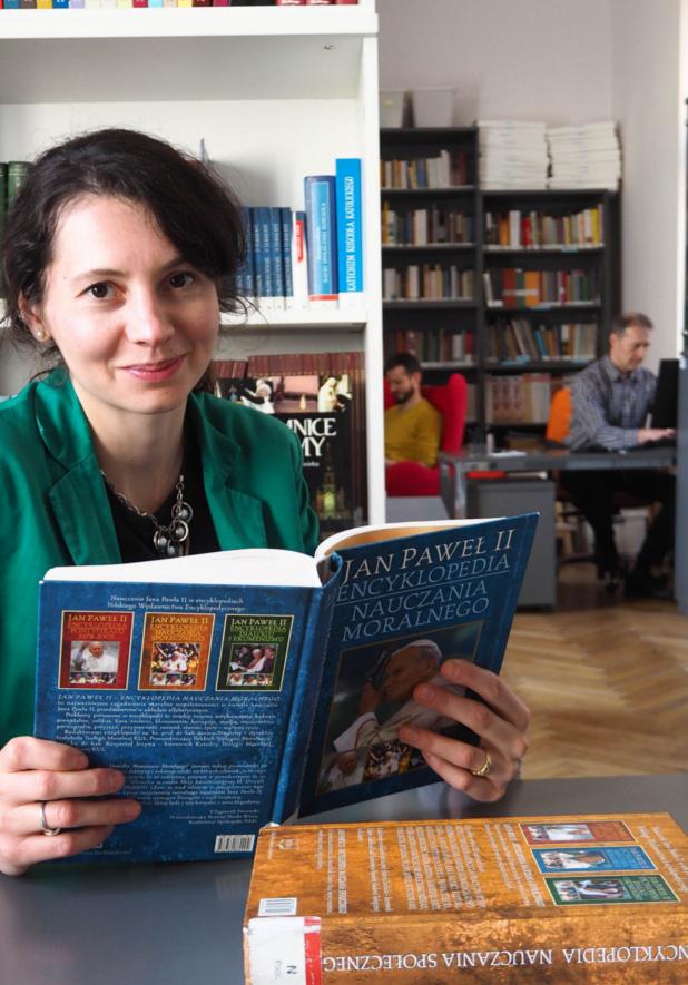 młoda dziewczyna czytająca księżkę w bibliotece, w tle dwaj mężczyźni pracujący na komputerze