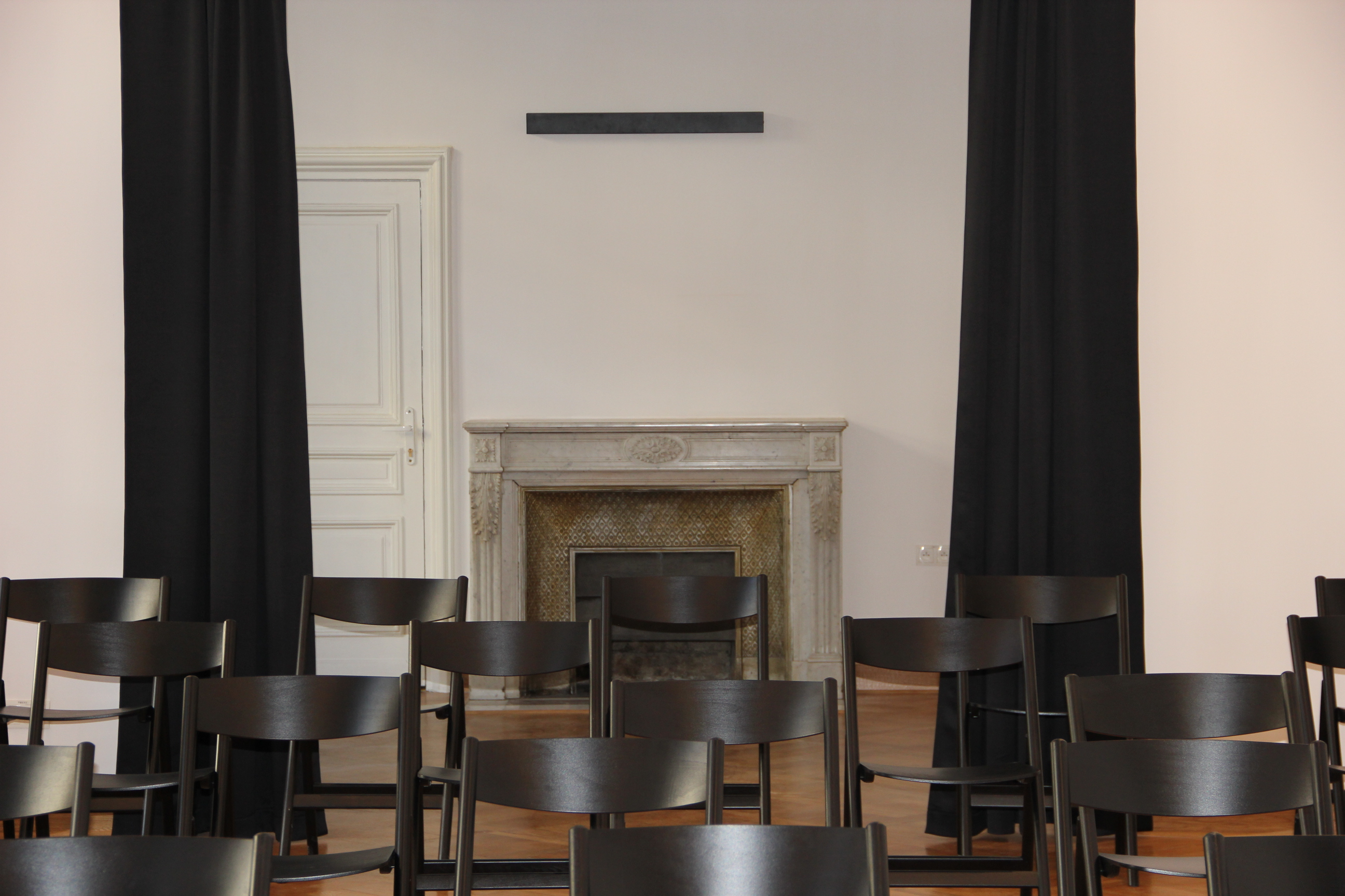 sala z dużą ilością krzeseł, kominek na ścianie