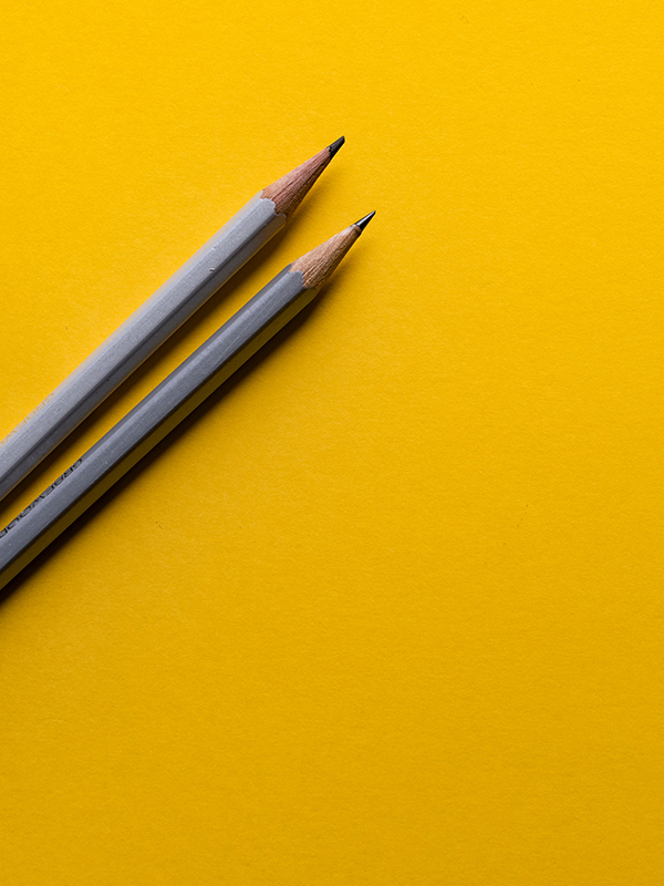 dwa ołówki na żółtym tle